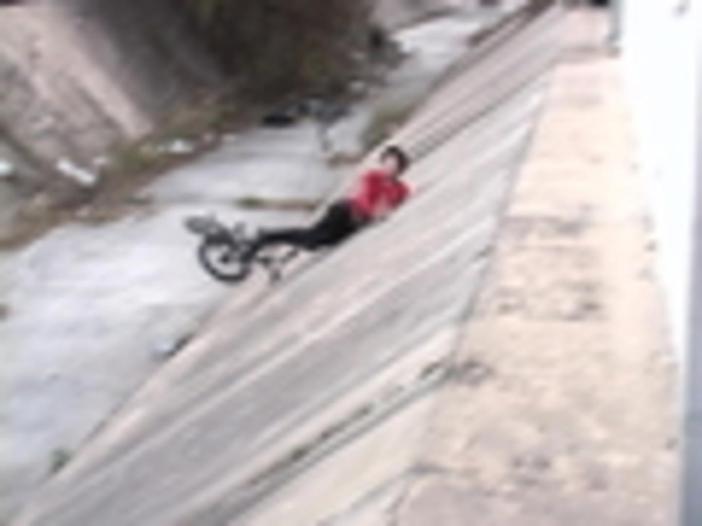 BMXer Jumps off Roof Into Drainage Ditch and Hits Wall
