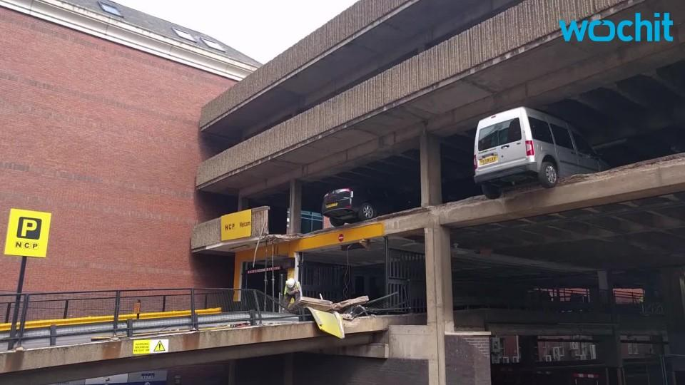 RAW: Cars hang in mid-air after wall collapses