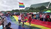 Thai protesters wave LGBT flag at anti-government rally during heavy rain